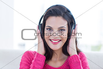 Smiling beautiful brunette relaxing on the couch and listening music