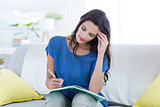 Thoughtful beautiful brunette writing in diary