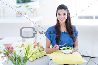 Smiling beautiful brunette sitting on the couch and eating salad