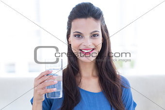 Smiling beautiful brunette sitting on the couch and holding glass of water