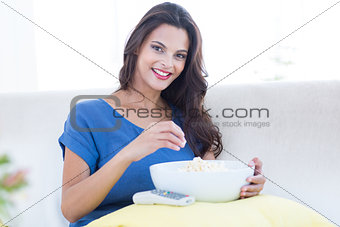 Smiling beautiful brunette relaxing on the couch with bowl of popcorn