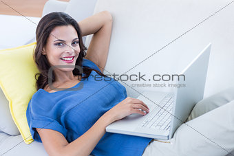 Smiling beautiful brunette relaxing on the couch and using her laptop