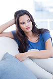 Thoughtful beautiful brunette sitting on the couch