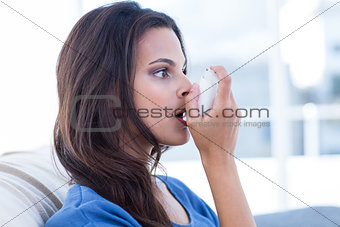 Beautiful brunette using inhaler