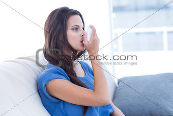 Beautiful brunette using inhaler