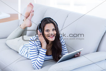 Smiling beautiful brunette listening music while using her tablet