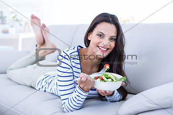 Smiling beautiful brunette relaxing on the couch and eating salad
