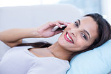 Smiling beautiful brunette relaxing on the couch and speaking on the phone