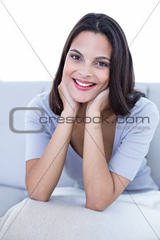 Smiling beautiful brunette sitting on the couch