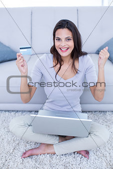 Smiling beautiful brunette sitting on the floor and doing online shopping