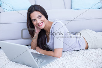 Smiling beautiful brunette lying on the floor and using her laptop