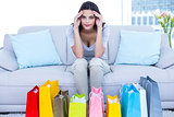 Worried brunette sitting on the couch with shopping bags