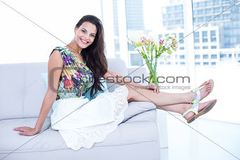 Smiling beautiful brunette sitting on the couch and looking at camera