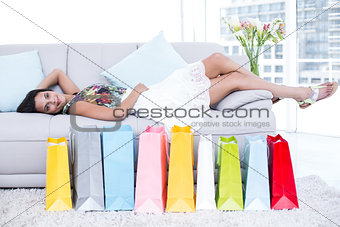 Smiling beautiful brunette lying on the couch with shopping bags around her