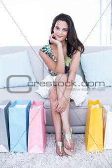 Smiling beautiful brunette sitting on the couch with shopping bags around her