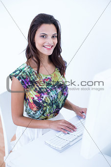 Smiling beautiful brunette using her computer