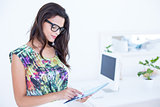 Smiling beautiful brunette standing in front of her computer