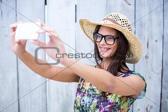 Smiling beautiful brunette taking selfie