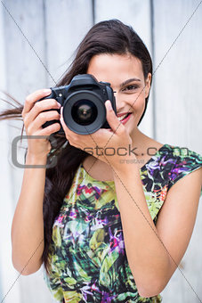 Smiling beautiful brunette taking pictures