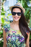 Smiling beautiful brunette wearing straw hat and sun glasses