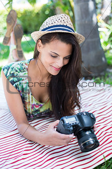 Smiling beautiful brunette lying on the blanket and taking pictures