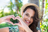 Smiling beautiful brunette doing heart shape with her hands