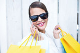 Pretty woman on the phone holding shopping bags