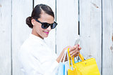 Pretty woman using her smartphone holding shopping bags