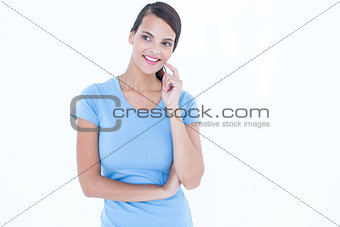 Thoughtful woman smiling with finger on cheek