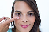 Beautiful woman applying contact lens