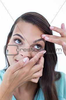 Beautiful woman applying contact lens