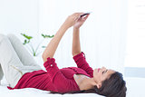 Beautiful woman using her smartphone lying on bed