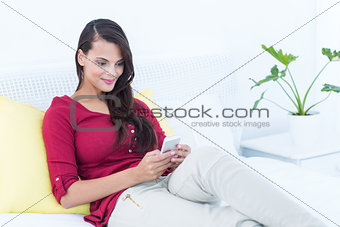 Beautiful woman using her smartphone sitting on bed