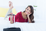 Beautiful woman with a suitcase lying on her bed