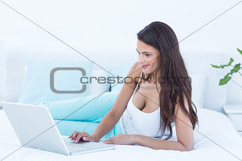 Beautiful woman using laptop on her bed