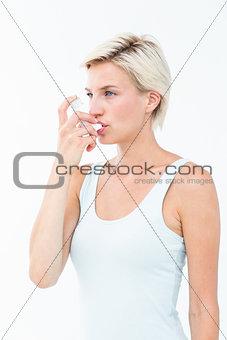Blonde woman taking her inhaler