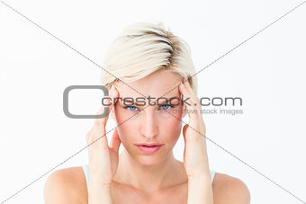 Beautiful blonde suffering from headache looking at camera