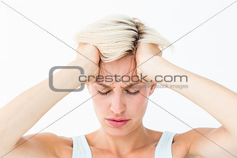 Blonde woman suffering from headache holding her head