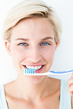 Happy blonde looking at camera holding toothbrush