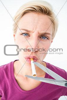 Beautiful blonde cutting a cigarette
