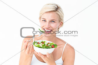 Beautiful blonde woman eating salad