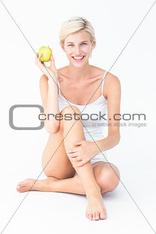 Sitting woman holding an apple