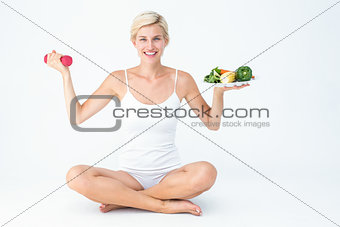 Attractive woman holding vegetables plate and dumbbell