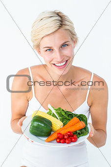 Beautiful woman holding vegetables plate