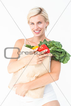 Attractive woman holding bag of vegetables