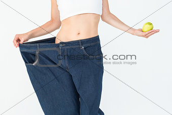 Slim woman wearing too big jeans holding an apple