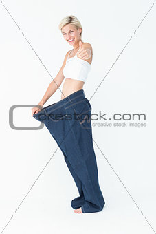 Blonde wearing too large pants with the thumb up