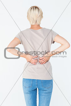 Blonde woman having a back ache and holding her back