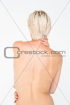 Beautiful topless woman touching her back