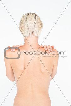 Beautiful topless woman touching her shoulders